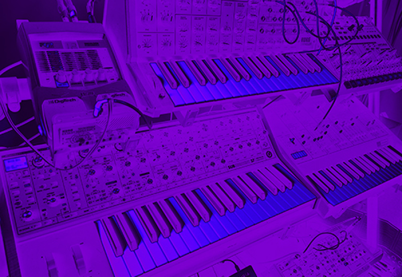 blue tinted photo of keyboard stand with three synthesisers