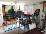 gallery view from inside with paintings on display panels and studio in background